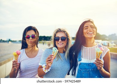 Three joyful young girlfriends on a promenade standing in a row smiling happily as they enjoy takeaway ice cream cones on summer vacation