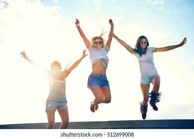Three joyful young women leaping in the air celebrating the freedom of their summer vacation backlit by a bright sun flare