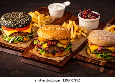 Three Juicy Homemade Beef Cheeseburger on a Wooden Board. Assortment of burgers with beef and cheese on a dark background.