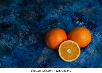 Three juicy oranges lying on a blue countertop. Citrus fruit and free space for text.