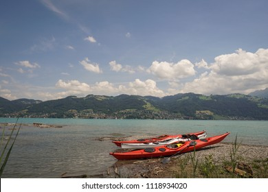 Three kayaks lying on a gravel beach with drift wood and ice blue lake and mountains in background