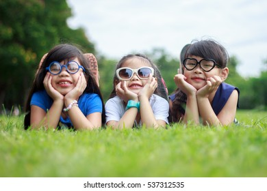 Three kid asian  lying on the lawn with head in hands and looking at the camera