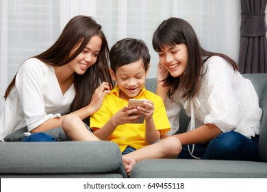Three kids Asian family, one boy and two girls are playing together with happiness in home, using smarthphone to listen music and watch video
