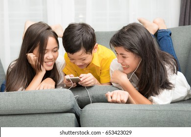 Three kids Asian family, one boy and two girls are relaxing and playing together with happiness in home, using smarthphone to listen music and watch video