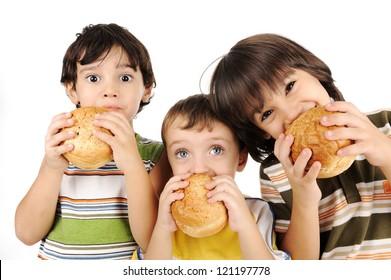 Three kids eating burgers