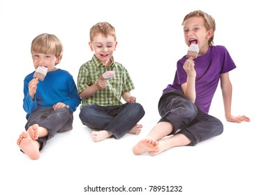three kids eating ice lolly on white background