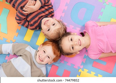 Three kids having fun lying on backs on alphabet mat.