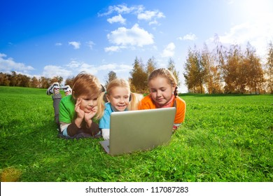 Three kids with laptop in sunny autumn park