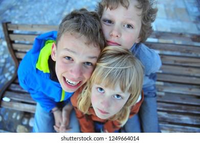 Three kids looking at camera, top view