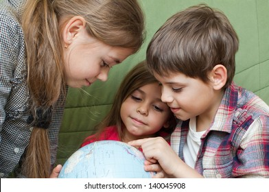 Three kids looking closely at a world globe