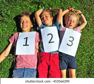 Three kids lying on the grass with the numbers. Outdoors scene after children competition