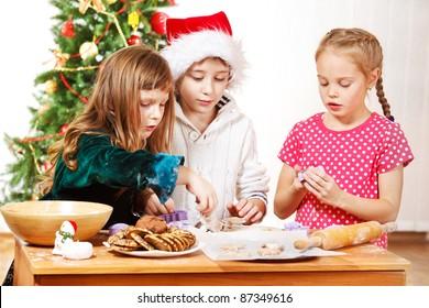 Three kids making Christmas cookies