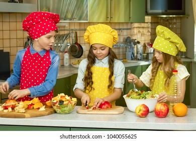 Three kids making salad, kitchen. Cut fruits and vegetables.