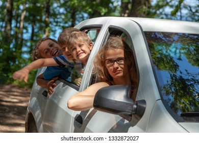 Three kids and mother looking out the window of car. Family road trip.