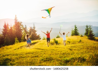 Three kids in the mountains at sunset play kite and butterfly fishing net. Happy summer holidays and childhood.