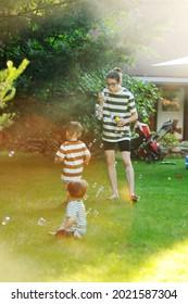 Trois enfants de 1, 2 et 15 ans en tenue rayée jouant avec des bulles de savon sur l'herbe au coucher du soleil