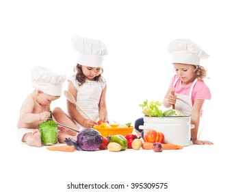 Three kids play with vegetables. Little chefs isolated on white
