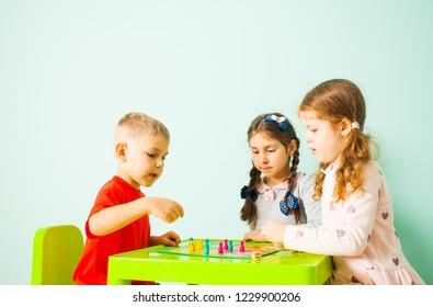 Three kids playing ludo game at home