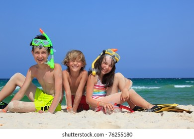 Three kids playing in the sand on the beach.
