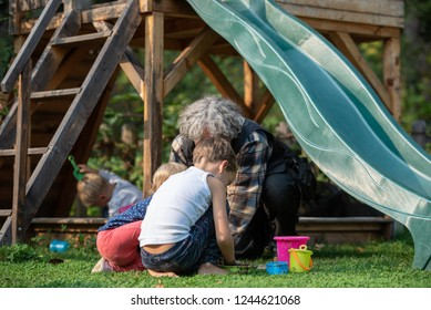 Three kids playing with their grandfather outside in backyard having fun.
