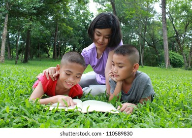 Three kids reading in the park.