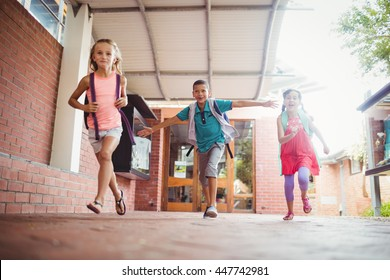 Three kids running in the playground on a sunny day