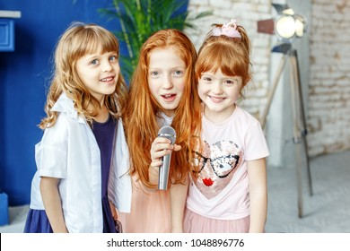 Three kids sing a song in a microphone. Group. The concept is childhood, lifestyle, music, singing, friendship.
