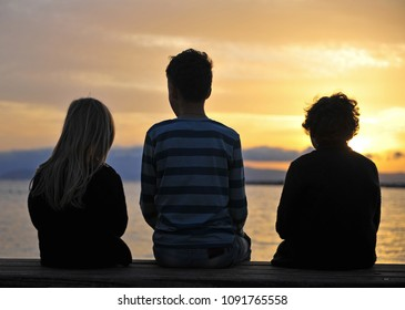 Three kids sitting by the sea on sunset