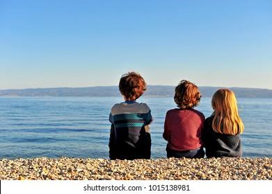 Three kids sitting on the beach on sunset