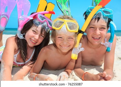 Three kids with snorkels and fins on the beach.