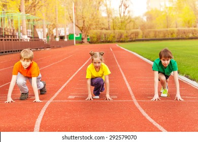Three kids stand with bended knee ready to run