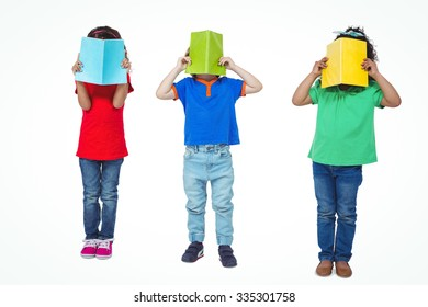 Three kids standing with books in front of their faces against a white background