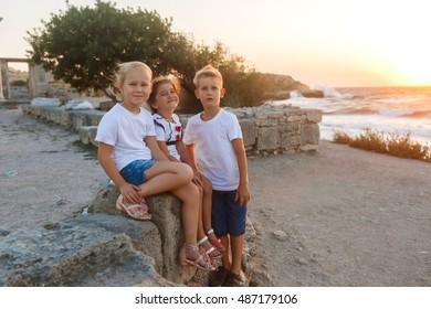 Three kids standing on beach at sunset