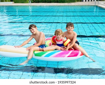 Three kids, two boys and toddler girl splash in an outdoors swimming pool in summer. Happy children, brothers and sister playing on huge inflatable gum lollipop enjoying sunny weather in public pool.