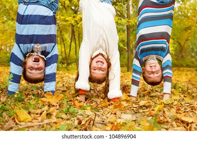 Three  kids upside down in autumn park