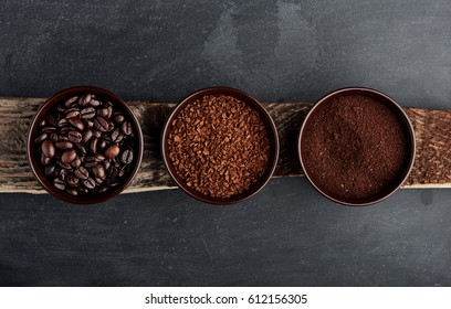 Three kinds of coffee: beans, milled, instant in cups on wooden plank.