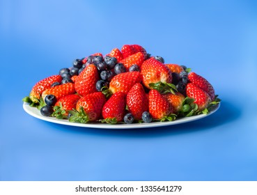 Three kinds of fresh berries on a white plate