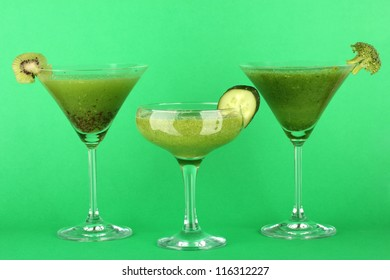 Three kinds of green juice in coctail glasses on color background