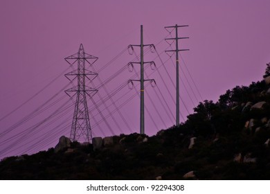 Three kinds of power poles and lines at the ridge of the mountain. Purple sky at sunset.