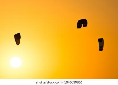 Three kites (kitesurfing) flying in sunset sky