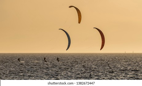 Three kitesurfers at sunset in front of Fremantle beach, Western Australia