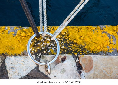 three knots attaching to one ring anchored on canal bank