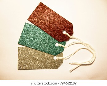 Three labels for a gift of sparkling silver, red and green material with a rope on white background side view