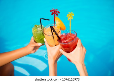 Three ladies cheering with tasty nectars with ice cubes, with black straws, palms decoration, in swim pool, transparent clean clear blue water, sun shines, smooth tanned skin, carefree festive mode