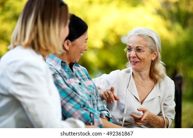 Three ladies having a funny conversation in the park. Selective focus on one person.