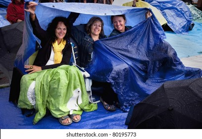 Three Ladies At An Outdoor Music Concert (Folkfest) Protecting Themselves Under Tarps From The Rain; Edmonton, Alberta, Canada