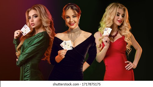 Three ladies in stylish dresses and jewelry. They smiling, showing playing cards, posing against colorful background. Poker, casino. Close-up