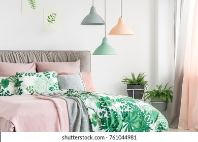 Three lamps in pastel colors hanging above bed with soft bedhead in bright interior