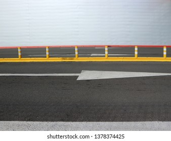 Three lane road with a row of yellow street poles and a  white wall on background. Copy space