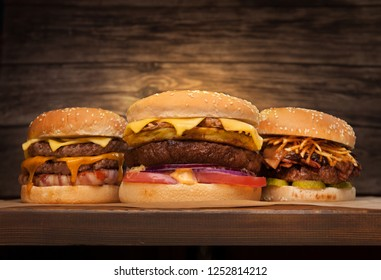 Three large burgers on wooden background. Low angle front view. Copy space for your text.